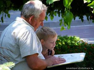 Дед с внуком читают книгу